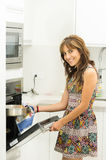 Woman wearing colorful dress in modern kitchen opening oven door holding mittens and cooking pot of metal smiling to Stock Image