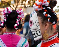 Woman wearing colorful skull mask and hair ribbons for Dia de Los Muertos/Day of the Dead. Young woman colorful skull mask and hair ribbons for Dia de Los royalty free stock images