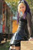 Woman wearing corset on trainplatform. Gothic woman with blond long hair in black corset and latex mini skirt leaning against a wall of a train platform Royalty Free Stock Photos