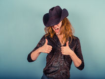 Woman wearing cowboy hat giving thumbs up Royalty Free Stock Photos