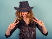 Woman wearing cowboy hat showing peace sign Royalty Free Stock Images