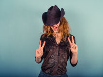 Woman wearing cowboy hat showing peace sign Stock Photos
