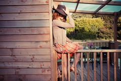 Woman wearing cowboy hat sitting on porch Stock Image