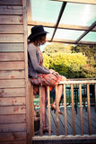 Woman wearing cowboy hat sitting on porch Stock Images