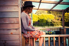 Woman wearing cowboy hat sitting on porch Royalty Free Stock Photos