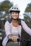 Woman wearing cycling helmet and pink hooded sports top, sitting on bicycle, smiling, portrait Stock Photography