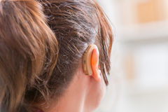 Woman wearing deaf aid. Young woman wearing deaf aid royalty free stock photos