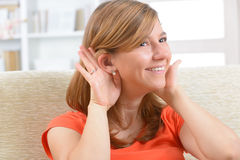 Woman wearing deaf aid. Young, smiling woman wearing deaf aid Stock Image