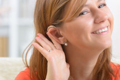Woman wearing deaf aid stock photo