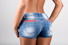 Woman wearing denim shorts with a beautiful waist. Studio shot Stock Photos