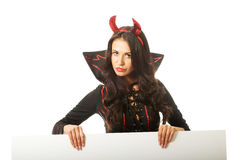 Woman wearing devil clothes holding white empty banner Stock Images