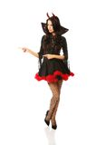 Woman wearing devil clothes pointing left Royalty Free Stock Photography