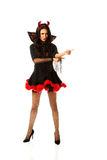 Woman wearing devil clothes pointing to the corner Stock Images