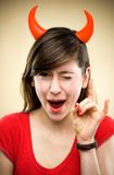Woman wearing devil horns. Portrait of a young woman in studio Stock Photo