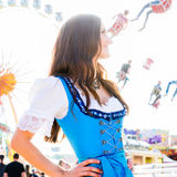 Woman wearing dirndl standing in front of ferris wheel. Dirndl wearing woman is standing in front of ferris wheel and carousel at Bavarian folk festival stock photography