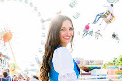 Woman wearing dirndl standing in front of ferris wheel. Dirndl wearing woman is standing in front of ferris wheel and carousel at Bavarian folk festival stock image