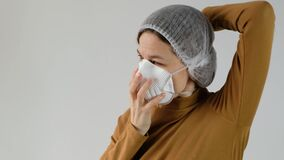 Woman wearing disposable cup and filter mask respirator for pollution and personal protection on white background.