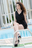 Woman wearing dress and heels sits on pool deck stairs. Woman wearing black short dress and heels front of hotel's swimming pool, sits on pool deck stairs with Stock Images
