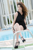 Woman wearing dress and heels sits on pool deck stairs. Woman wearing black short dress and heels front of hotel's swimming pool, sits on pool deck stairs with Royalty Free Stock Image