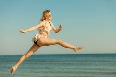 Woman wearing dress playing, jumping near sea Royalty Free Stock Photos