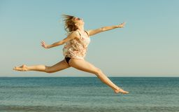 Woman wearing dress playing, jumping near sea Royalty Free Stock Photo