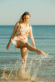 Woman wearing dress playing with water in sea. Summertime fun conept. Woman wearing short dress playing and having fun with water, enjoying summer vacation Stock Images