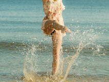 Woman wearing dress playing with water in sea. Summertime fun conept. Woman wearing short dress playing and having fun with water, enjoying summer vacation Royalty Free Stock Image