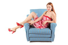 Woman wearing dress sitting in striped armchair. Royalty Free Stock Images