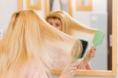 Woman wearing dressing gown brushing her hair Royalty Free Stock Photo