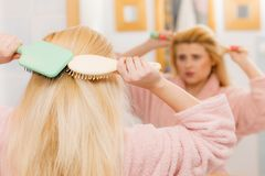 Woman wearing dressing gown brushing her hair Stock Images