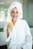 woman wearing a dressing gown drinking a glass of juice Stock Images