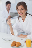 Woman wearing a dressing gown having breakfast Royalty Free Stock Image