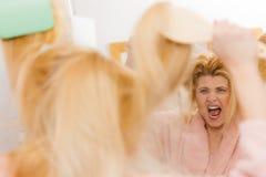 Shocked woman wearing dressing gown brushing her hair Stock Image