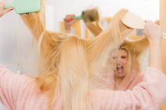 Shocked woman wearing dressing gown brushing her hair Stock Photo