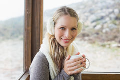 Woman wearing earmuff with cup against window Stock Photo