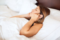 Woman wearing earplugs in bed Royalty Free Stock Images