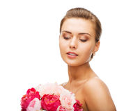 Woman wearing earrings and holding flowers Royalty Free Stock Images