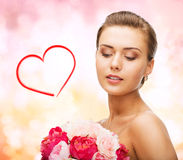 Woman wearing earrings and holding flowers Stock Photo