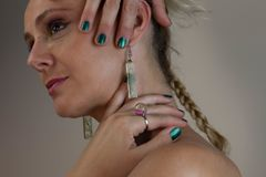 Woman Wearing Earrings While Holding Her Neck royalty free stock images