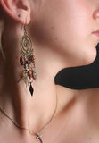 Woman wearing earrings. Profile of woman with sophisticated Earrings and necklet  with a cross Stock Images