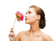 Woman wearing earrings and smelling flower Stock Photos