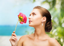 Woman wearing earrings and smelling flower Royalty Free Stock Images