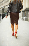 Woman wearing elegant skirt and red high heel shoes in old town. Young beautiful business woman walking,urban background. Back view of a fashion shopper woman royalty free stock photos