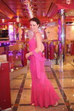 Woman wearing evening dress standing in hall Stock Photography