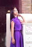 Woman wearing evening dress standing near big classic drawers Stock Image