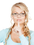 Woman wearing eyeglasses with finger on her lips Stock Photos