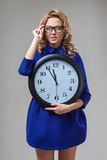 Woman wearing eyeglasses holding big clock Royalty Free Stock Photos