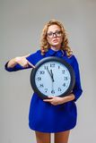 Woman wearing eyeglasses holding big clock Stock Photo