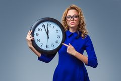 Woman wearing eyeglasses holding big clock Royalty Free Stock Images