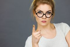 Woman wearing eyeglasses pointing at camera stock photography